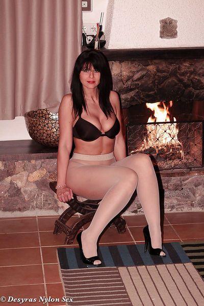 Brunette nylon model Desyra Noir posing non nude beside fireplace