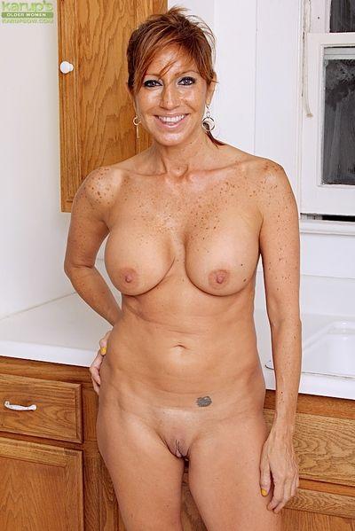Busty mature Latina Tara Holiday exposes big natural tits in kitchen