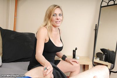 Steamy mature blonde jerking a stiff cock for cum on her smiley face