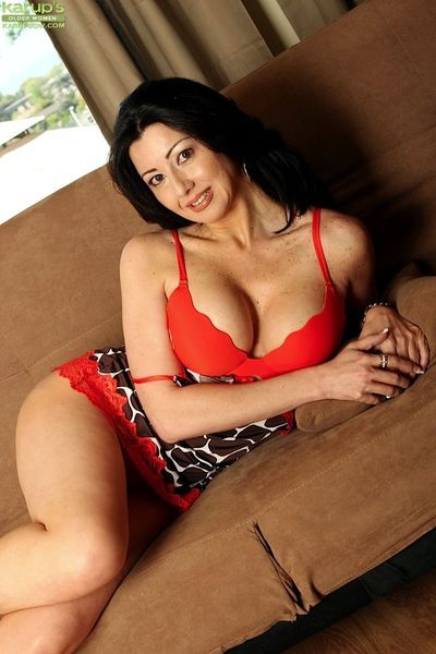 Mature brunette woman in lingerie and high heels baring big natural boobs