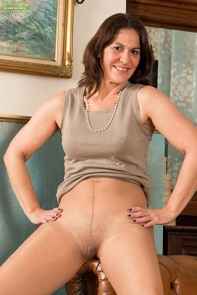 Mature first timer pulls her pantyhose down around ankles to model nude