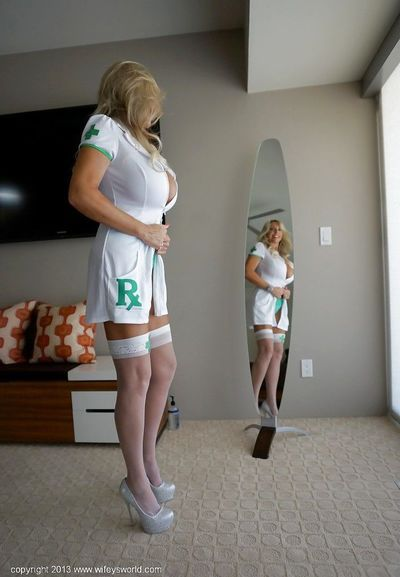 Playful mature vixen in stockings gets rid of her sexy nurse uniform
