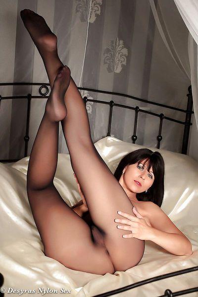 European lady Desyra Noir modeling topless on bed in black nylons