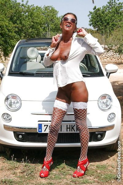 Naughty mature UK woman Lady Sarah modeling topless outdoors in fishnets