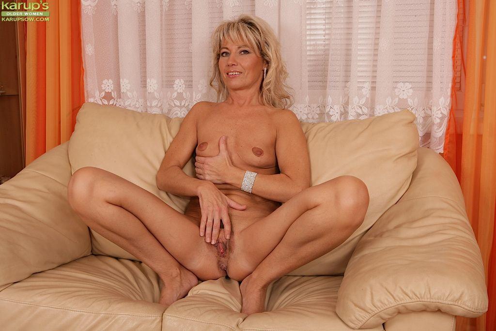 Older blonde Janet Darling sliding a finger into her granny pussy