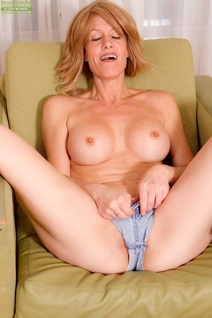 Bubbied mature lady Lana Wilder getting naked and teasing her cunt