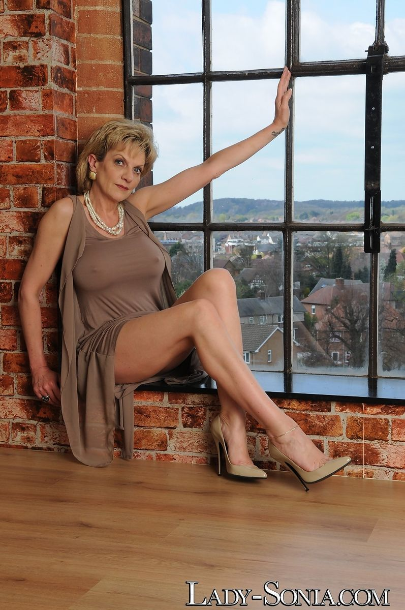 Non nude mature woman Lady Sonia shows bare legs in front of window in heels