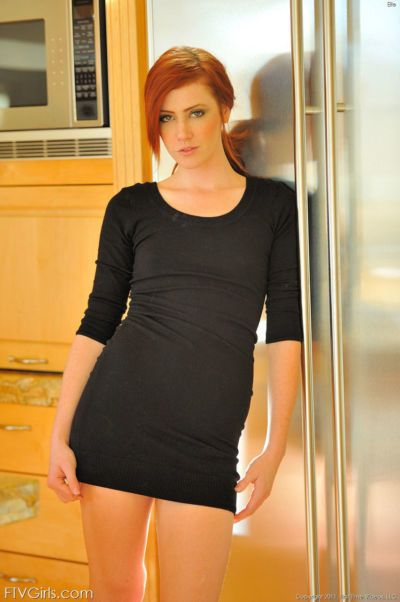 Natural redhead hikes her black dress and sticks a toy in her pussy
