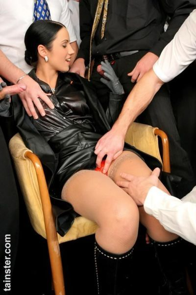 Clothed slut in leather overcoat gets pissed on by a group of men