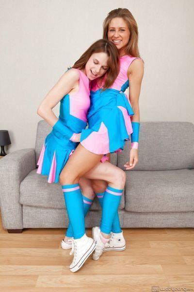 Lovely teen cheerleaders in knee socks have some lesbian fun on a sofa
