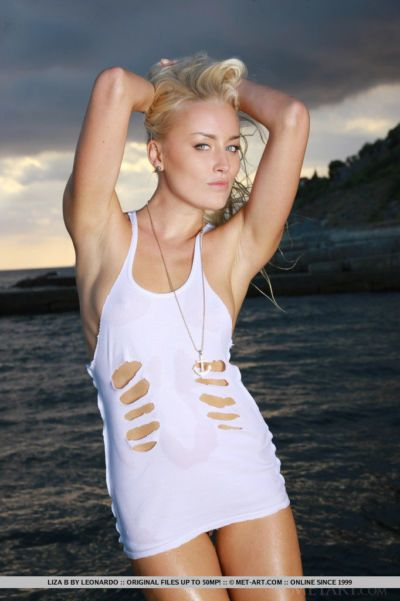 Blond solo model Liza B removing ripped dress to pose in the nude on the beach
