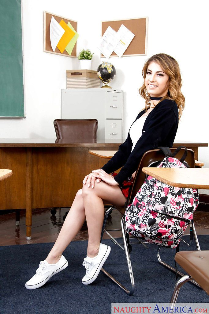 Cute coed Kristen Scott stripping off schoolgirl uniform on school desk