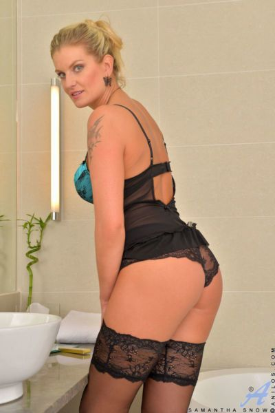 Blonde MILF strips off sexy lingerie and stockings to pose nude in bathroom