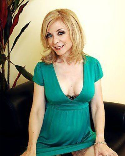 Mature lady Nina Hartley denudes ripe melons and poses in stockings