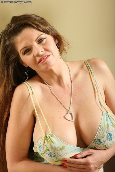 Mature brunette with jaw-dropping gorgeous tits getting rid of her lingerie