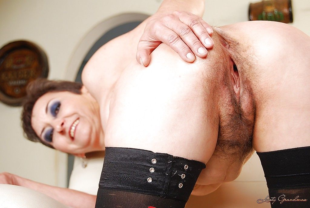 Skinny granny in stockings posing topless and uncovering her unshaven cunt
