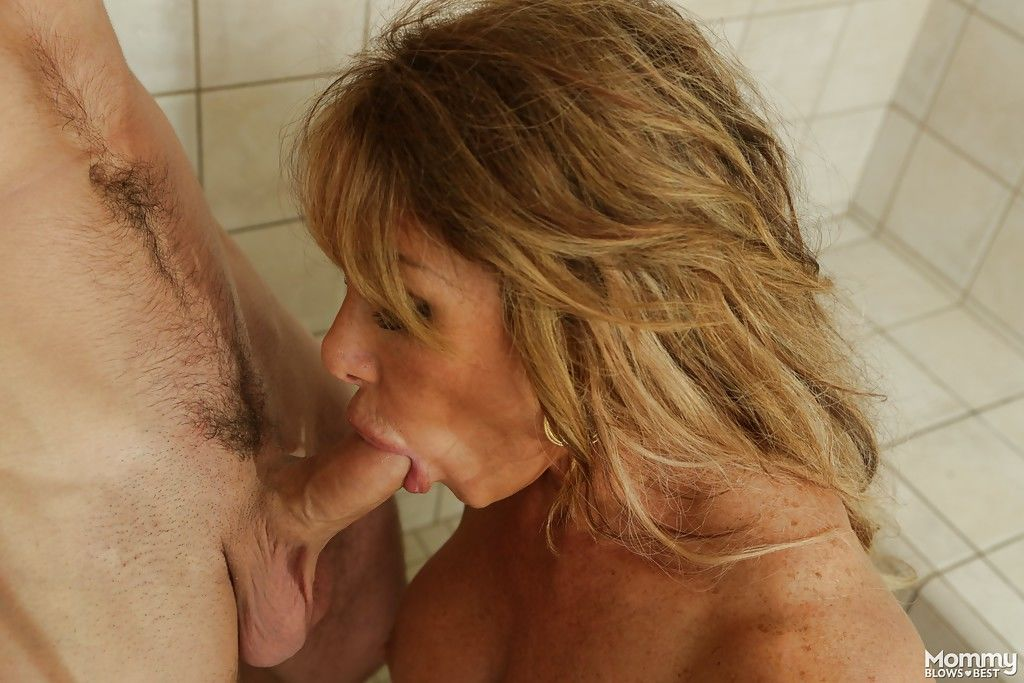 Busty MILF Farrah Dahl kneels to suck heavy cock in the shower