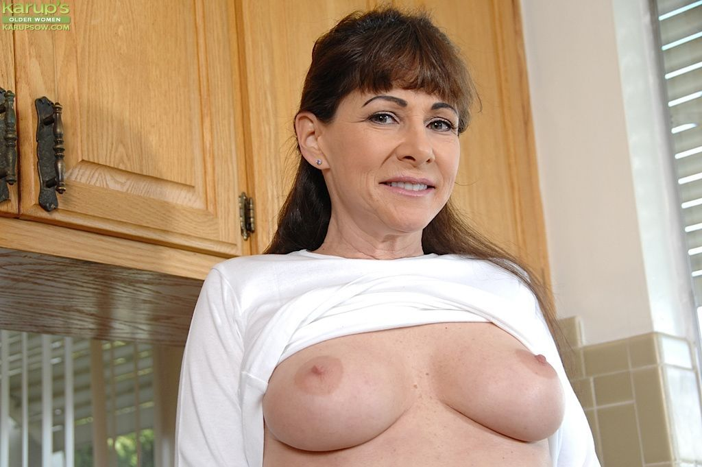 Mature woman Alexandra Silk revealing big tits and pierced cunt in kitchen
