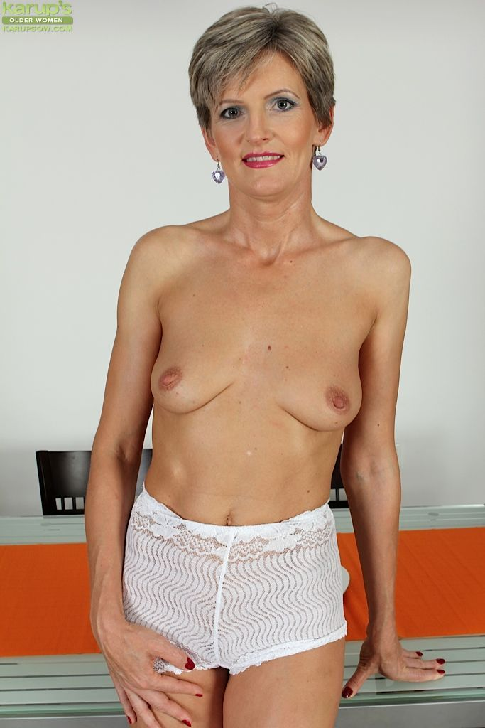 Hot mature Melanie spreads her older pussy lips wide at the dining table