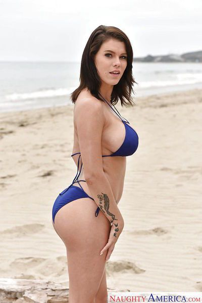 Brunette solo girl Peta Jensen letting fake tits free from bikini on beach