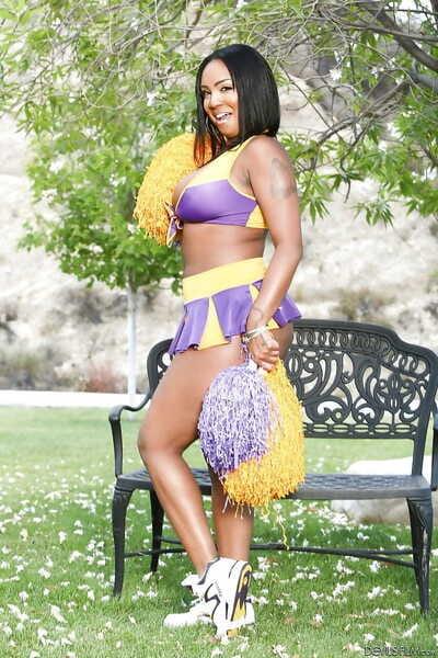 Phat cheerleader Layton Benton showing off her big natural pom poms in garden