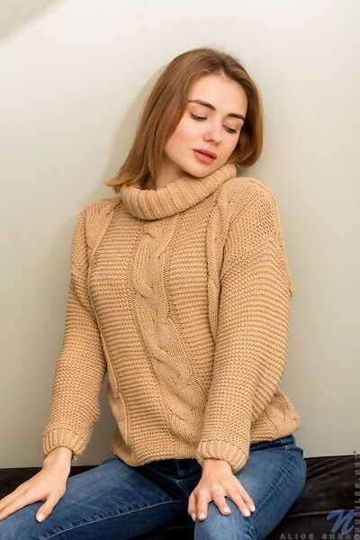 Young redhead Alice Shea removes jeans and sweater to model in the nude