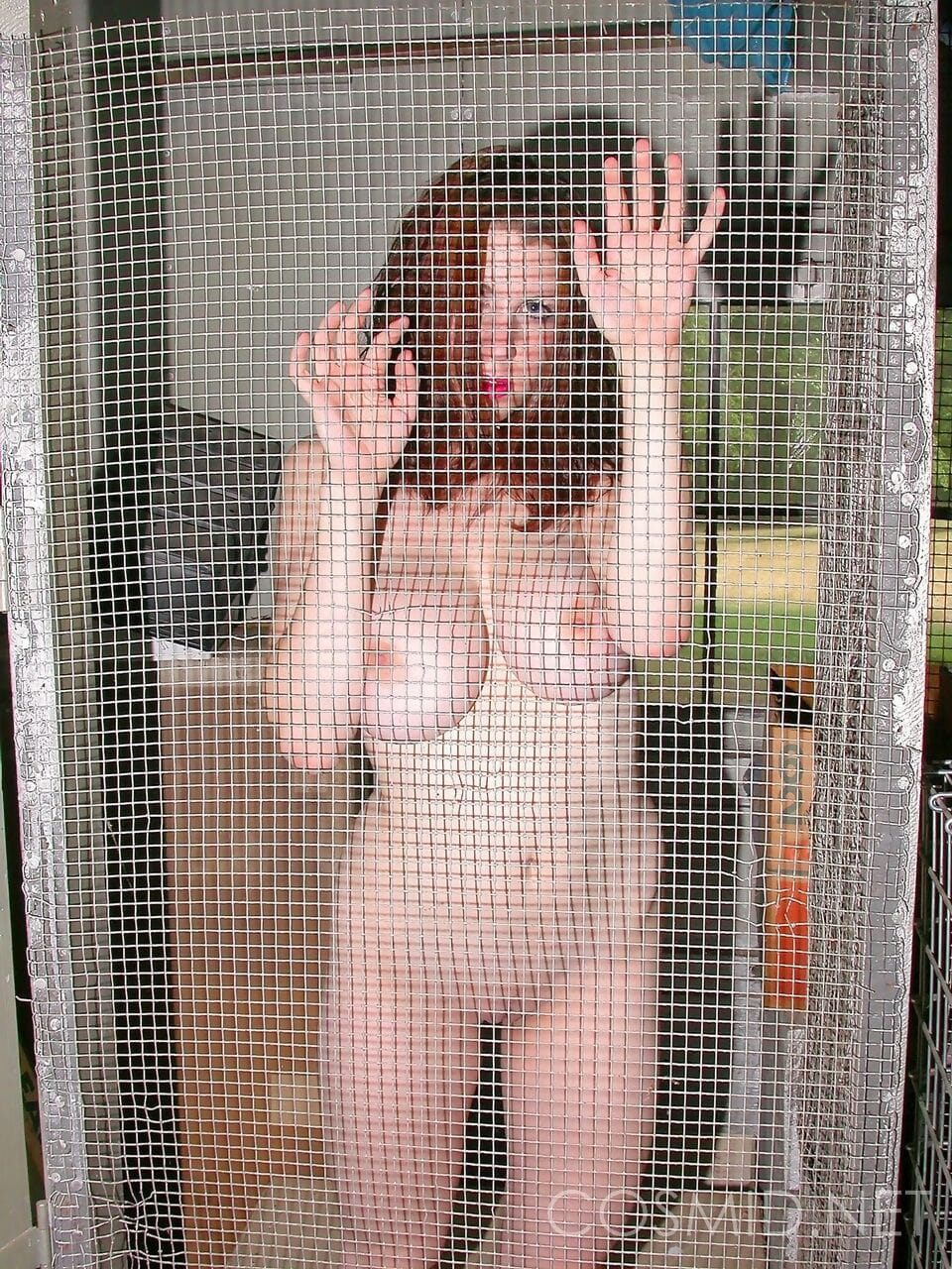 Redhead amateur removes see thru clothes for nude poses afore a window