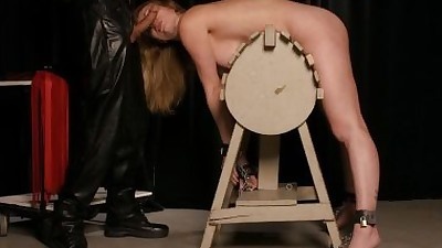 Blonde female is restrained to a..