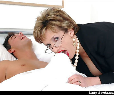Lusty mature lady in glasses licking and sucking a cock covered by a sheet