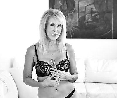 Mature solo model Erica Lauren spreads her fishnet clad legs to masturbate