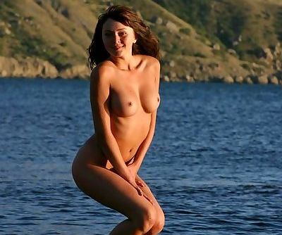 At sunset a naked girl with a sexy body hangs out on the rocks